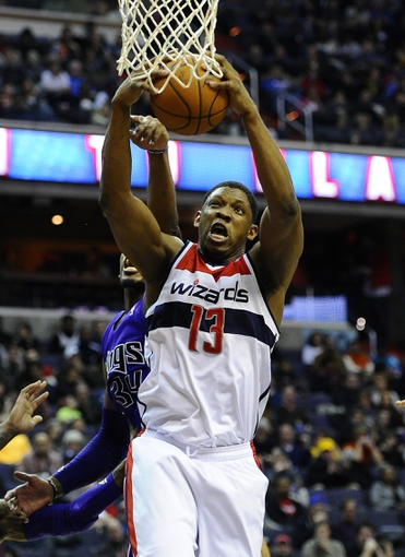 Feb 9, 2014; Washington, DC, USA; Washington Wizards center Kevin Seraphin (13) grabs a rebound over Sacramento Kings power forward Jason Thompson (34) during the first half at Verizon Center. Mandatory Credit: Brad Mills-USA TODAY Sports