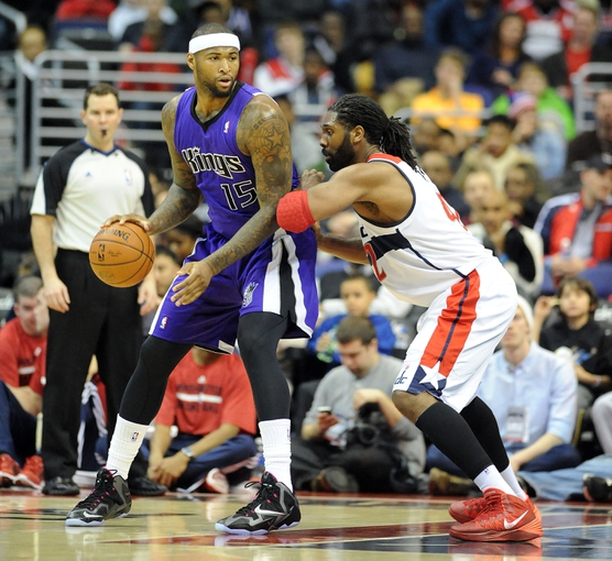 Feb 9, 2014; Washington, DC, USA; Sacramento Kings center DeMarcus Cousins (15) dribbles the ball as Washington Wizards power forward Nene Hilario (42) defends during the first half at Verizon Center. Mandatory Credit: Brad Mills-USA TODAY Sports