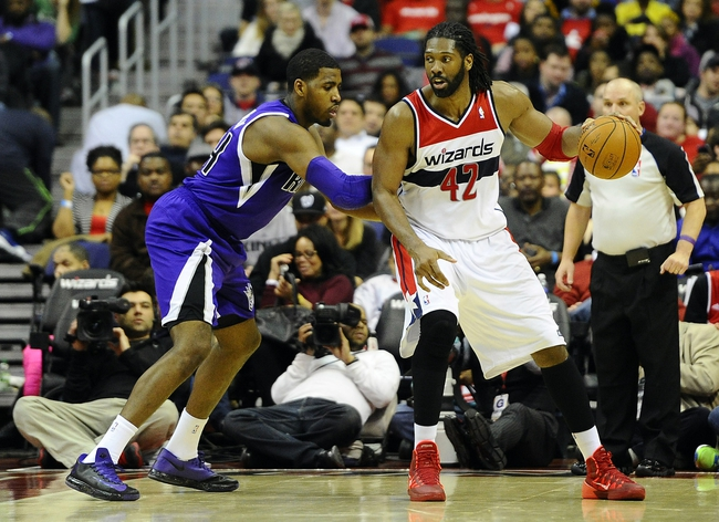 Feb 9, 2014; Washington, DC, USA; Washington Wizards power forward Nene Hilario (42) dribbles as Sacramento Kings power forward Jason Thompson (34) defends during the second half at Verizon Center. The Wizards defeated the Kings 93 - 84. Mandatory Credit: Brad Mills-USA TODAY Sports