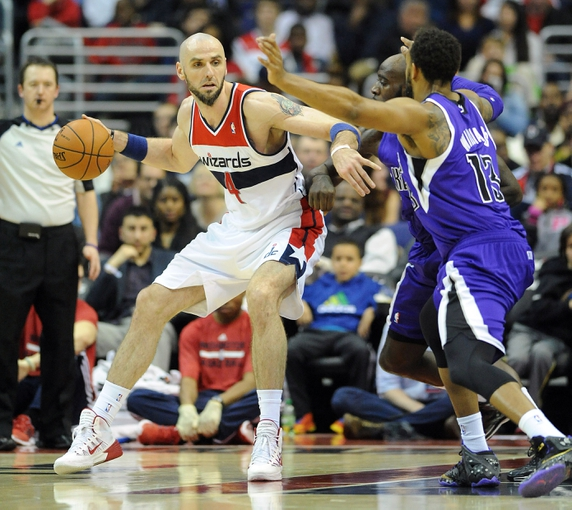 Feb 9, 2014; Washington, DC, USA; Washington Wizards center Marcin Gortat (4) dribbles as Sacramento Kings power forward Derrick Williams (13) and Sacramento Kings small forward Quincy Acy (5) defend during the second half at Verizon Center. The Wizards defeated the Kings 93 - 84. Mandatory Credit: Brad Mills-USA TODAY Sports