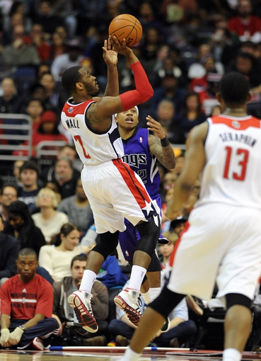 Feb 9, 2014; Washington, DC, USA; Washington Wizards point guard John Wall (2) attempts a shot as Sacramento Kings point guard Isaiah Thomas (22) defends during the second half at Verizon Center. The Wizards defeated the Kings 93 - 84. Mandatory Credit: Brad Mills-USA TODAY Sports