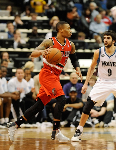 Feb 8, 2014; Minneapolis, MN, USA; Portland Trail Blazers guard Damian Lillard (0) drives up court against Minnesota Timberwolves guard Ricky Rubio (9) in the second half at Target Center. The Trail Blazers defeated the Wolves  117-110.  Mandatory Credit: Marilyn Indahl-USA TODAY Sports