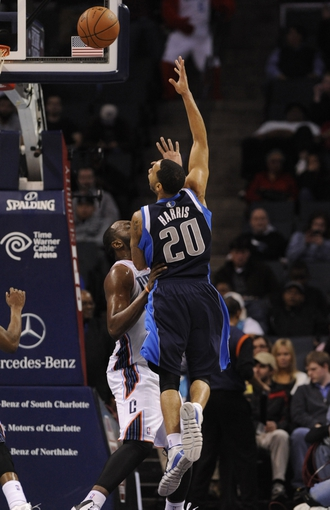 Feb 11, 2014; Charlotte, NC, USA; Dallas Mavericks guard Devin Harris (20) shoots the ball over Charlotte Bobcats center Al Jefferson (25) during the second half at Time Warner Cable Arena. The Bobcats won 114-89. Mandatory Credit: Sam Sharpe-USA TODAY Sports