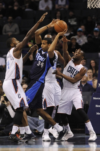 Feb 11, 2014; Charlotte, NC, USA; Dallas Mavericks forward Brandan Wright (34) holds the ball as Charlotte Bobcats defense of forward Michael Kidd-Gilchrist (14), center Al Jefferson (25), and guard Kemba Walker (15) defend during the second half at Time Warner Cable Arena. The Bobcats won 114-89. Mandatory Credit: Sam Sharpe-USA TODAY Sports