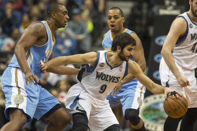 Feb 12, 2014; Minneapolis, MN, USA; Minnesota Timberwolves point guard Ricky Rubio (9) controls the ball away from Denver Nuggets power forward Darrell Arthur (00) in the first half at Target Center. Mandatory Credit: Jesse Johnson-USA TODAY Sports