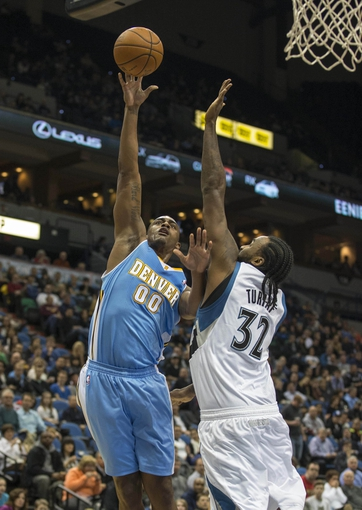 Feb 12, 2014; Minneapolis, MN, USA; Denver Nuggets power forward Darrell Arthur (00) goes up for a shot over Minnesota Timberwolves center Ronny Turiaf (32) in the first half at Target Center. Mandatory Credit: Jesse Johnson-USA TODAY Sports