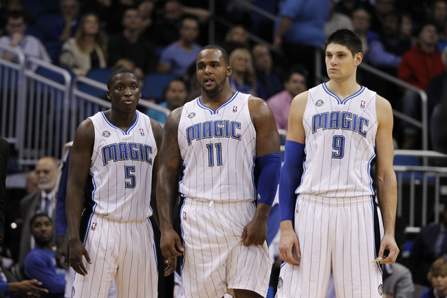 Feb 12, 2014; Orlando, FL, USA; Orlando Magic shooting guard Victor Oladipo (5), power forward Glen Davis (11) and center Nikola Vucevic (9) look on as they wait as tghe referees look at a call during the second half at Amway Center. Memphis Grizzlies defeated the Orlando Magic 86-81. Mandatory Credit: Kim Klement-USA TODAY Sports