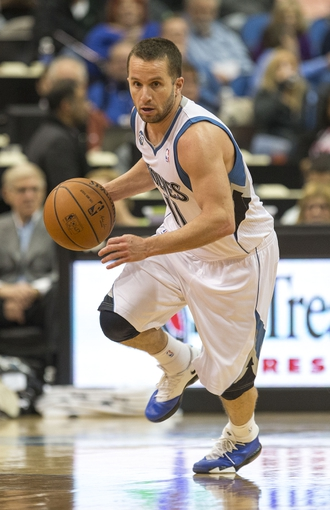 Feb 12, 2014; Minneapolis, MN, USA; Minnesota Timberwolves point guard J.J. Barea (11) dribbles the ball down the court in the second half against the Denver Nuggets at Target Center. The Timberwolves won 117-90. Mandatory Credit: Jesse Johnson-USA TODAY Sports