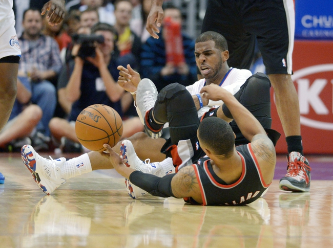 Feb 12, 2014; Los Angeles, CA, USA; Portland Trail Blazers guard Damian Lillard (0) and Los Angeles Clippers guard Chris Paul (3) play for the ball in the fourth quarter at Staples Center. The Clippers defeated the Trail Blazers 122-117. Mandatory Credit: Kirby Lee-USA TODAY Sports