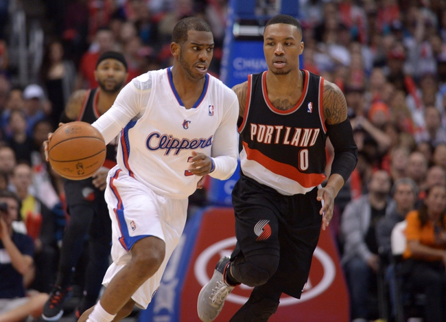 Feb 12, 2014; Los Angeles, CA, USA; Los Angeles Clippers guard Chris Paul (3) is defended by Portland Trail Blazers guard Damian Lillard (0) in the fourth quarter at Staples Center. The Clippers defeated the Trail Blazers 122-117. Mandatory Credit: Kirby Lee-USA TODAY Sports