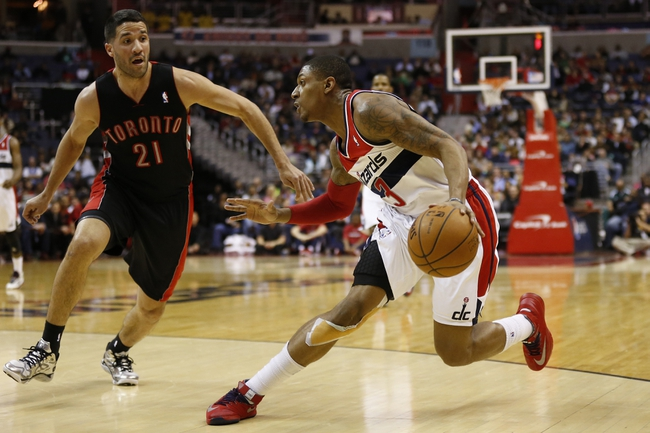 Feb 18, 2014; Washington, DC, USA; Washington Wizards shooting guard Bradley Beal (3) dribbles the ball as Toronto Raptors point guard Greivis Vasquez (21) defends in the second quarter at Verizon Center. Mandatory Credit: Geoff Burke-USA TODAY Sports