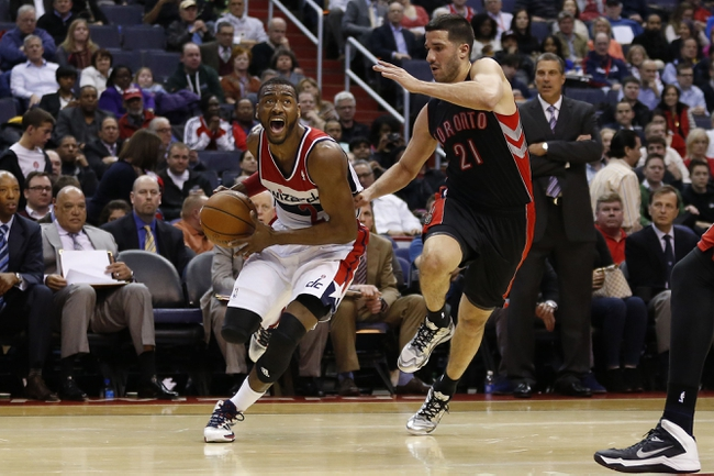 Feb 18, 2014; Washington, DC, USA; Washington Wizards point guard John Wall (2) dribbles the ball as Toronto Raptors point guard Greivis Vasquez (21) defends in the second quarter at Verizon Center. Mandatory Credit: Geoff Burke-USA TODAY Sports