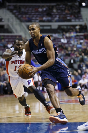 Feb 18, 2014; Auburn Hills, MI, USA; Charlotte Bobcats point guard Ramon Sessions (7) moves the ball defended by Detroit Pistons point guard Will Bynum (12) in the first half at The Palace of Auburn Hills. Mandatory Credit: Rick Osentoski-USA TODAY Sports
