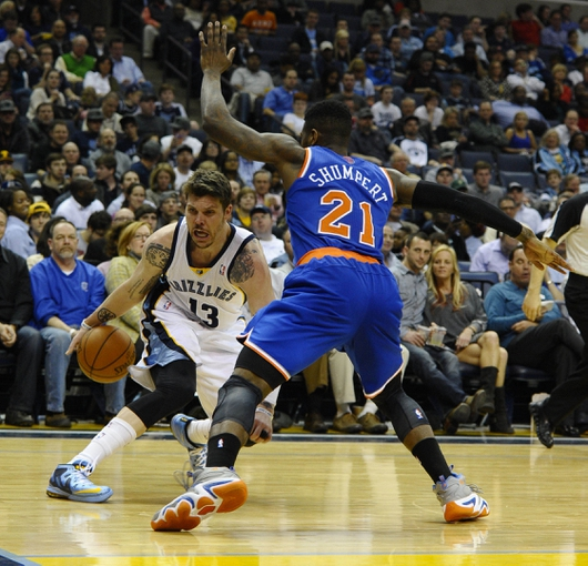 Feb 18, 2014; Memphis, TN, USA; Memphis Grizzlies small forward Mike Miller (13) handles the ball against New York Knicks shooting guard Iman Shumpert (21) during the second quarter at FedExForum. Mandatory Credit: Justin Ford-USA TODAY Sports