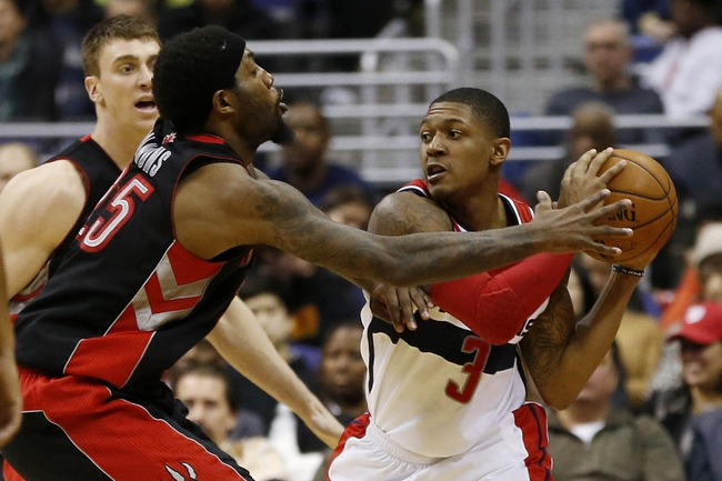 Feb 18, 2014; Washington, DC, USA; Washington Wizards shooting guard Bradley Beal (3) holds the ball as Toronto Raptors power forward Amir Johnson (15) defends in the fourth quarter at Verizon Center. The Raptors won 103-93. Mandatory Credit: Geoff Burke-USA TODAY Sports