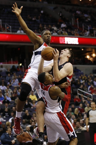 Feb 18, 2014; Washington, DC, USA; Toronto Raptors power forward Tyler Hansbrough (50) attempts to shoot the ball as Washington Wizards shooting guard Bradley Beal (3) and Wizards center Kevin Seraphin (13) defend in the fourth quarter at Verizon Center. The Raptors won 103-93. Mandatory Credit: Geoff Burke-USA TODAY Sports
