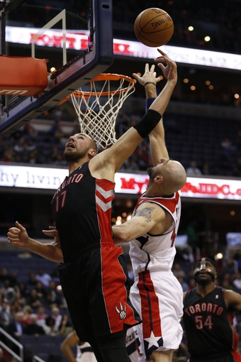 Feb 18, 2014; Washington, DC, USA; Washington Wizards center Marcin Gortat (4) shoots the ball as Toronto Raptors center Jonas Valanciunas (17) defends in the second quarter at Verizon Center. The Raptors won 103-93. Mandatory Credit: Geoff Burke-USA TODAY Sports
