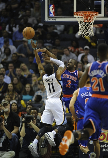 Feb 18, 2014; Memphis, TN, USA; Memphis Grizzlies point guard Mike Conley (11) shoots over New York Knicks point guard Raymond Felton (2) during the game at FedExForum. Memphis Grizzlies beat New York Knicks 98 - 93. Mandatory Credit: Justin Ford-USA TODAY Sports