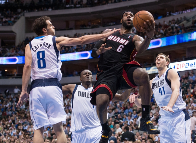 Feb 18, 2014; Dallas, TX, USA; Miami Heat small forward LeBron James (6) drives to the basket past Dallas Mavericks point guard Jose Calderon (8) and power forward Dirk Nowitzki (41) during the second half at the American Airlines Center. James leads his team with 42 points. The Heat defeated the Mavericks  117-106. Mandatory Credit: Jerome Miron-USA TODAY Sports