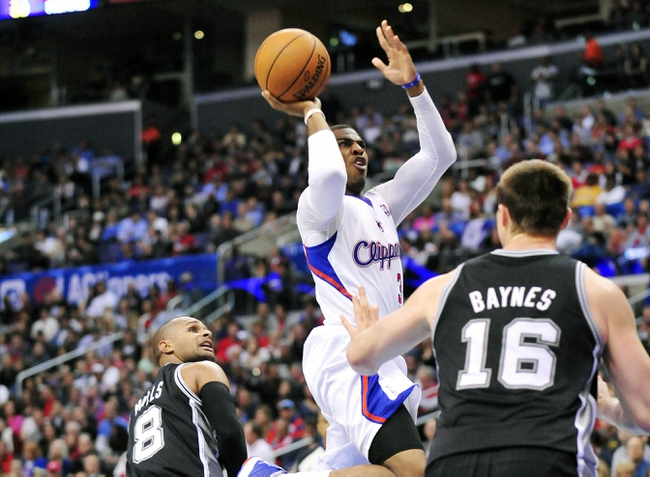 February 18, 2014; Los Angeles, CA, USA; Los Angeles Clippers point guard Chris Paul (3) moves to the basket against San Antonio Spurs point guard Patty Mills (8) and power forward Aron Baynes (16) during the first half at Staples Center. Mandatory Credit: Gary A. Vasquez-USA TODAY Sports