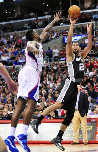 February 18, 2014; Los Angeles, CA, USA; San Antonio Spurs power forward Tim Duncan (21) shoots against Los Angeles Clippers center DeAndre Jordan (6) during the second half at Staples Center. Mandatory Credit: Gary A. Vasquez-USA TODAY Sports