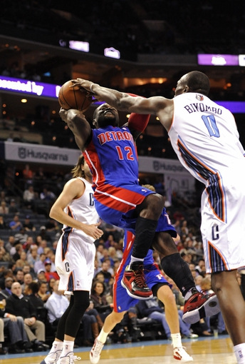 Feb 19, 2014; Charlotte, NC, USA; Detroit Pistons guard Will Bynum (12) drives to the basket and gets fouled by Charlotte Bobcats forward center Bismack Biyombo (0) during the first half of the game at Time Warner Cable Arena. Mandatory Credit: Sam Sharpe-USA TODAY Sports
