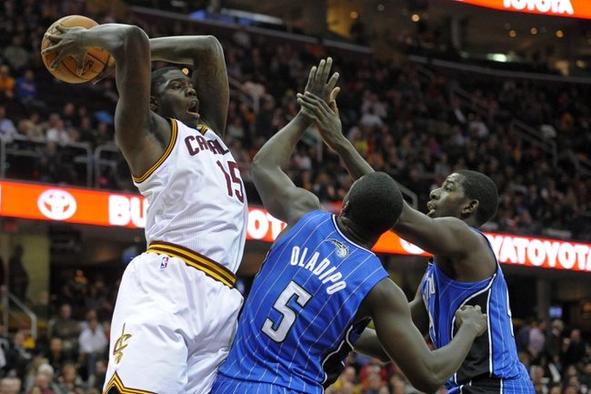 Feb 19, 2014; Cleveland, OH, USA; Cleveland Cavaliers small forward Anthony Bennett (15) rebounds against Orlando Magic shooting guard Victor Oladipo (5) and power forward Andrew Nicholson (44) in the fourth quarter at Quicken Loans Arena. Mandatory Credit: David Richard-USA TODAY Sports