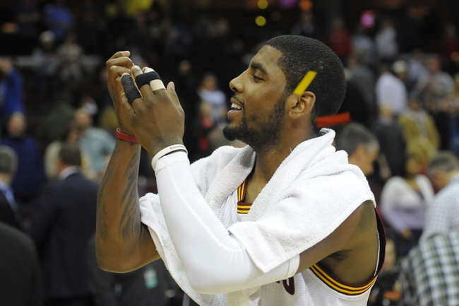 Feb 19, 2014; Cleveland, OH, USA; Cleveland Cavaliers point guard Kyrie Irving (2) catches a piece of confetti after a 101-93 win over the Orlando Magic at Quicken Loans Arena. Mandatory Credit: David Richard-USA TODAY Sports