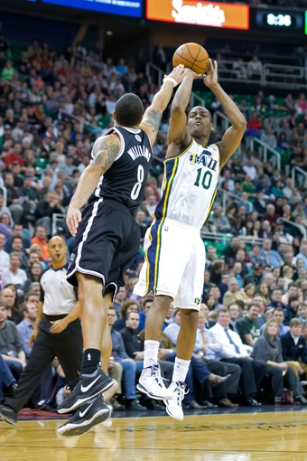 Feb 19, 2014; Salt Lake City, UT, USA; Utah Jazz point guard Alec Burks (10) shoots over Brooklyn Nets point guard Deron Williams (8) during the second half at EnergySolutions Arena. The Nets won 105-99. Mandatory Credit: Russ Isabella-USA TODAY Sports
