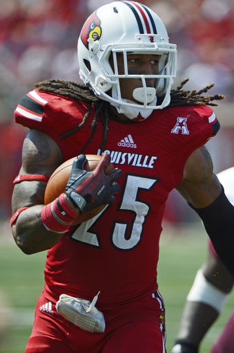 Sep 7, 2013; Louisville, KY, USA; Louisville Cardinals safety Calvin Pryor (25) runs back an interception during the second quarter against Eastern Kentucky Colonels at Papa John's Cardinal Stadium. Louisville defeated Eastern Kentucky 44-7.  Mandatory Credit: Jamie Rhodes-USA TODAY Sports