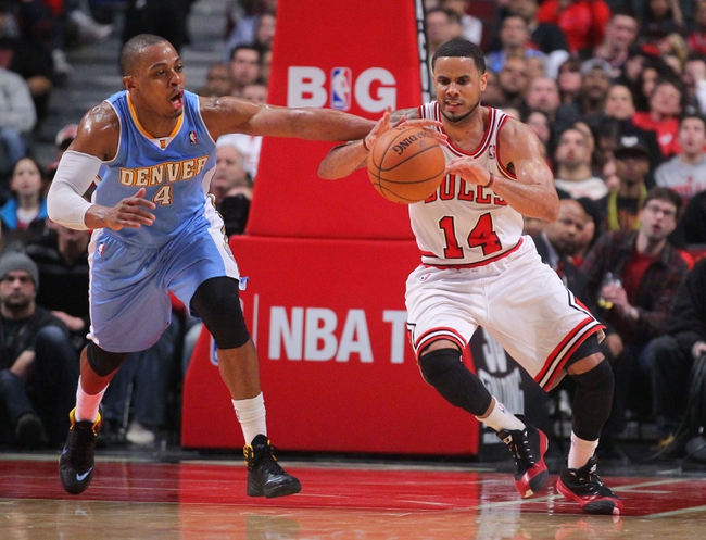 Feb 21, 2014; Chicago, IL, USA; Chicago Bulls point guard D.J. Augustin (14) and Denver Nuggets shooting guard Randy Foye (4) battle for the ball during the second quarter at the United Center. Mandatory Credit: Dennis Wierzbicki-USA TODAY Sports