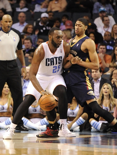Feb 21, 2014; Charlotte, NC, USA; Charlotte Bobcats center Al Jefferson (25) dribbles the ball as New Orleans Pelicans forward center Anthony Davis (23) defends during the second half at Time Warner Cable Arena. The Bobcats won 90-87.  Mandatory Credit: Sam Sharpe-USA TODAY Sports