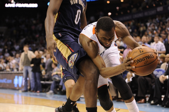 Feb 21, 2014; Charlotte, NC, USA; Charlotte Bobcats guard Kemba Walker (15) gets fouled by New Orleans Pelicans forward Al-Farouq Aminu (0) during the second half of the game at Time Warner Cable Arena. Bobcats win 90-87. Mandatory Credit: Sam Sharpe-USA TODAY Sports