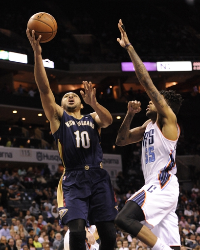 Feb 21, 2014; Charlotte, NC, USA; New Orleans Pelicans guard Eric Gordon (10) drives to the basket as he is defended by Charlotte Bobcats guard forward Chris Douglas-Roberts (55) during the second half of the game at Time Warner Cable Arena. Bobcats win 90-87. Mandatory Credit: Sam Sharpe-USA TODAY Sports
