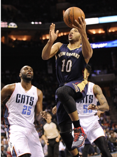Feb 21, 2014; Charlotte, NC, USA; New Orleans Pelicans guard Eric Gordon (10) drives to the basket as he is defended by Charlotte Bobcats center Al Jefferson (25) and guard forward Chris Douglas-Roberts (55) during the second half of the game at Time Warner Cable Arena. Bobcats win 90-87. Mandatory Credit: Sam Sharpe-USA TODAY Sports