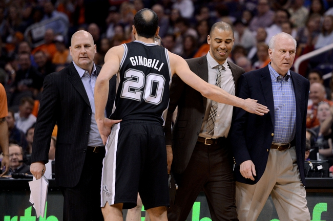 Feb 21, 2014; Phoenix, AZ, USA; San Antonio Spurs head coach Gregg Popovich is walked back to the bench after receiving a technical foul against the Phoenix Suns in the first half at US Airways Center. Mandatory Credit: Jennifer Stewart-USA TODAY Sports