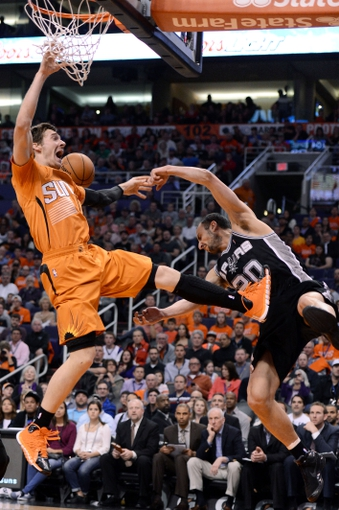 Feb 21, 2014; Phoenix, AZ, USA; Phoenix Suns guard Goran Dragic (1) commits an offensive foul as he goes up with the ball on San Antonio Spurs guard Manu Ginobili (20) in the first half at US Airways Center. Mandatory Credit: Jennifer Stewart-USA TODAY Sports