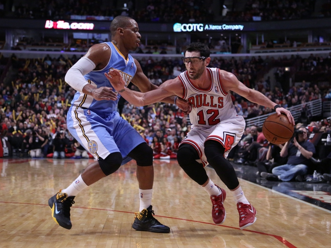 Feb 21, 2014; Chicago, IL, USA; Chicago Bulls shooting guard Kirk Hinrich (12) drives past Denver Nuggets shooting guard Randy Foye (4) during the second half at the United Center. Chicago won 117-89. Mandatory Credit: Dennis Wierzbicki-USA TODAY Sports