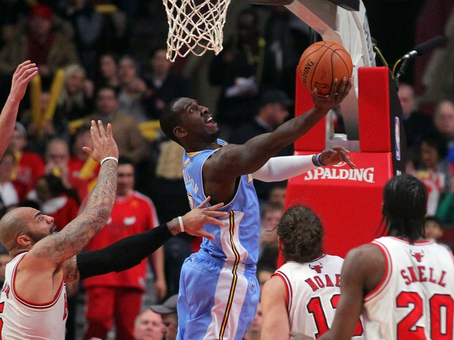 Feb 21, 2014; Chicago, IL, USA; Denver Nuggets center J.J. Hickson (7) scores past Chicago Bulls power forward Carlos Boozer (5) during the second half at the United Center. Chicago won 117-89. Mandatory Credit: Dennis Wierzbicki-USA TODAY Sports