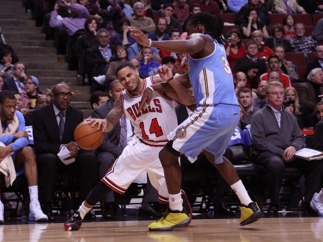 Feb 21, 2014; Chicago, IL, USA; Chicago Bulls point guard D.J. Augustin (14) is fouled by Denver Nuggets power forward Kenneth Faried (35) during the second half at the United Center. Chicago won 117-89. Mandatory Credit: Dennis Wierzbicki-USA TODAY Sports