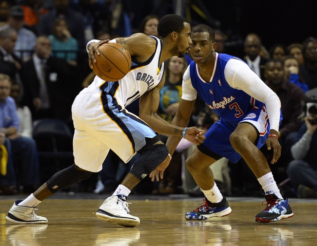 Feb 21, 2014; Memphis, TN, USA; Memphis Grizzlies point guard Mike Conley (11) dribbles the ball as Los Angeles Clippers point guard Chris Paul (3) defends at FedExForum. The Grizzlies won 102 - 96. Mandatory Credit: Justin Ford-USA TODAY Sports