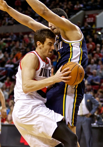 Feb 21, 2014; Portland, OR, USA; Portland Trail Blazers power forward Victor Claver (18) collides with Utah Jazz center Enes Kanter (0) during the second quarter at the Moda Center. Mandatory Credit: Craig Mitchelldyer-USA TODAY Sports