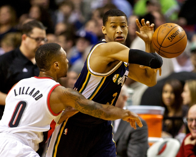 Feb 21, 2014; Portland, OR, USA; Portland Trail Blazers point guard Damian Lillard (0) knocks the ball away from Utah Jazz point guard Trey Burke (3) during the second quarter at the Moda Center. Mandatory Credit: Craig Mitchelldyer-USA TODAY Sports