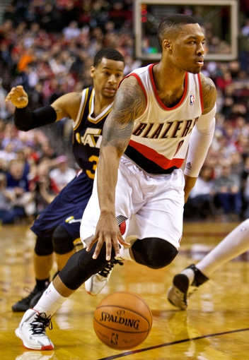Feb 21, 2014; Portland, OR, USA; Portland Trail Blazers point guard Damian Lillard (0) drives past Utah Jazz point guard Trey Burke (3) during the second quarter at the Moda Center. Mandatory Credit: Craig Mitchelldyer-USA TODAY Sports