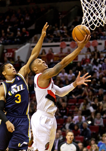 Feb 21, 2014; Portland, OR, USA; Portland Trail Blazers point guard Damian Lillard (0) shoots over Utah Jazz point guard Trey Burke (3) during the second quarter at the Moda Center. Mandatory Credit: Craig Mitchelldyer-USA TODAY Sports