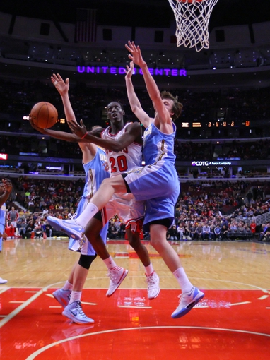 Feb 21, 2014; Chicago, IL, USA; Chicago Bulls shooting guard Tony Snell (center) scores between Denver Nuggets center Timofey Mozgov (left) and power forward Jan Vesely (right)  during the second half at the United Center. Chicago won 117-89. Mandatory Credit: Dennis Wierzbicki-USA TODAY Sports