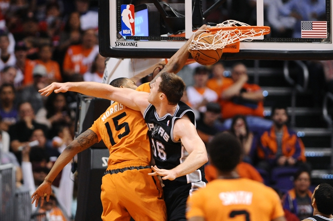 Feb 21, 2014; Phoenix, AZ, USA; Phoenix Suns forward Marcus Morris (15) dunks the ball over San Antonio Spurs forward Aron Baynes (16) in the second half at US Airways Center. The Suns defeated the Spurs 106-85. Mandatory Credit: Jennifer Stewart-USA TODAY Sports