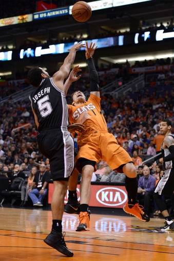 Feb 21, 2014; Phoenix, AZ, USA; San Antonio Spurs guard Cory Joseph (5) blocks Phoenix Suns guard Goran Dragic (1) in the first half at US Airways Center. The Suns defeated the Spurs 106-85. Mandatory Credit: Jennifer Stewart-USA TODAY Sports