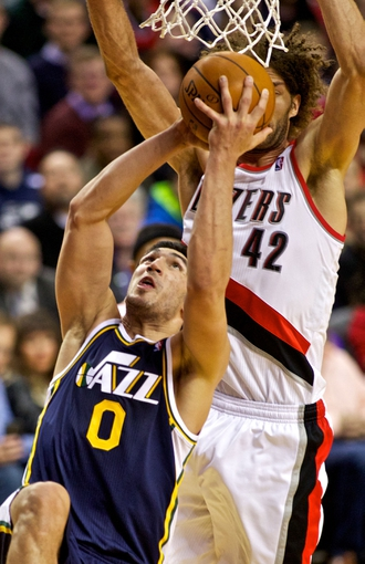 Feb 21, 2014; Portland, OR, USA; Utah Jazz center Enes Kanter (0) shoots over Portland Trail Blazers center Robin Lopez (42) during the fourth quarter at the Moda Center. Mandatory Credit: Craig Mitchelldyer-USA TODAY Sports