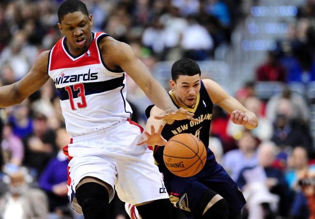Feb 22, 2014; Washington, DC, USA; Washington Wizards forward Kevin Seraphin (13) fights for a loose ball with New Orleans Pelicans guard Austin Rivers (25) at Verizon Center. Mandatory Credit: Evan Habeeb-USA TODAY Sports